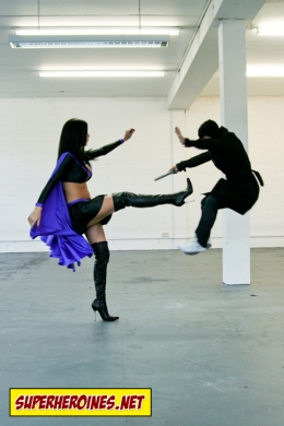 Superheroine Emma Glover kicking a man across the room