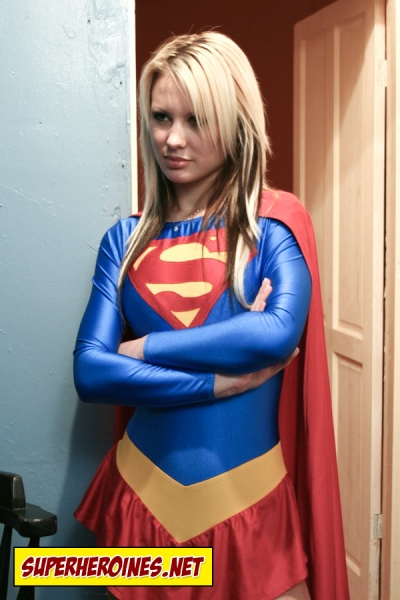 Teenage Supergirl standing with her arms folded